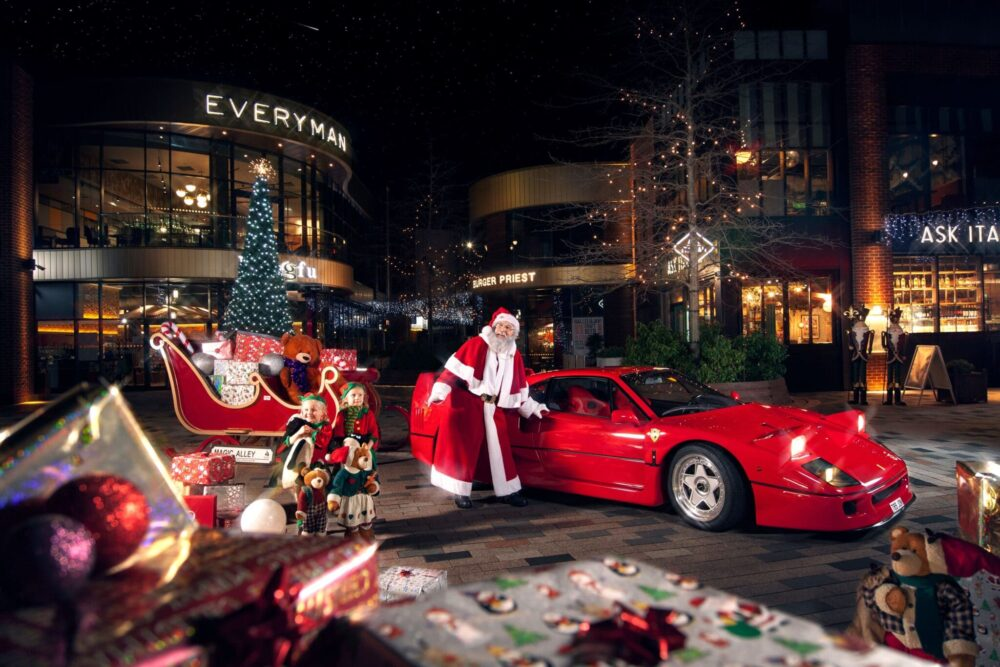 Santa standing in front of a ferrari