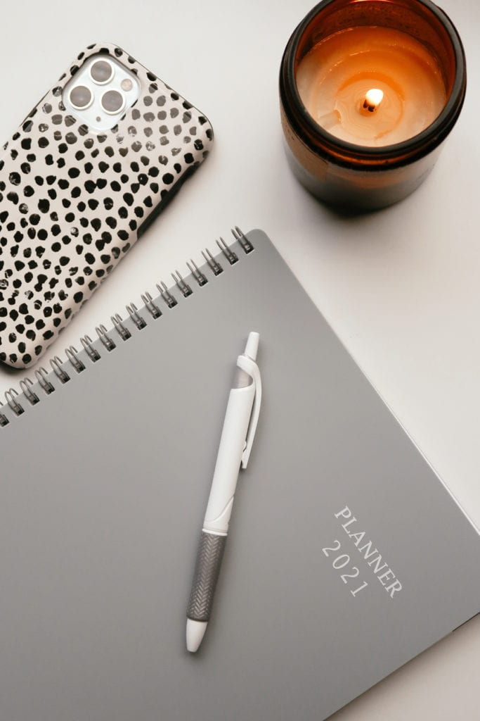 What does self care looks like in 2021 | Self Care Ideas by popular LA lifestyle blog, Tea Cups and Tulips: image of a grey planner, white pen, burning candle, and a smartphone with a black and white dot phone case.