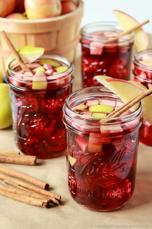 Mason Jars with Apple Cinnamon Sangria, garnished with cinnamon stick and apple slices