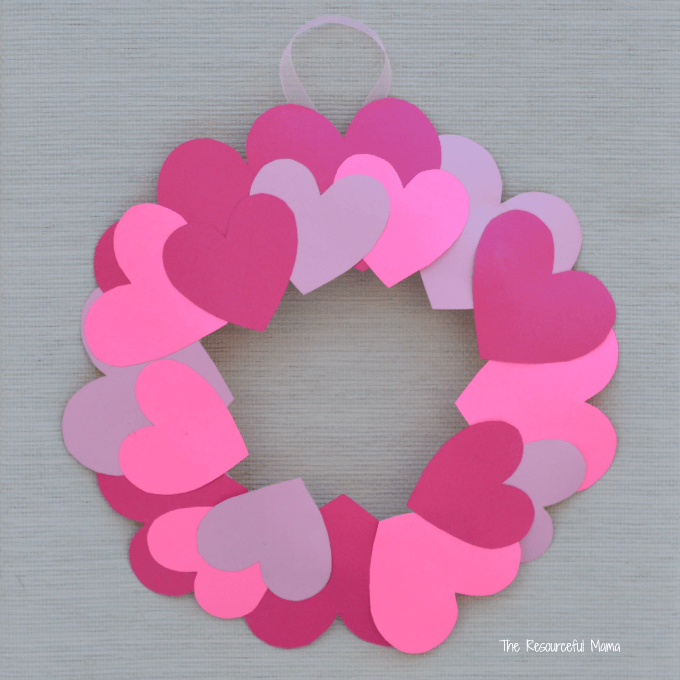 Paper hearts glued on paper plate with center cut out to create heart paper wreath