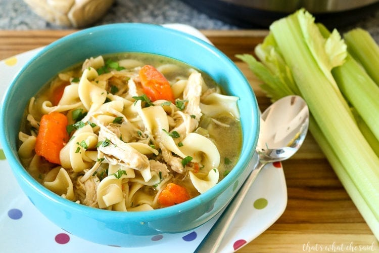 Easy Instant Pot Chicken Noodle Soup - Teal bowl of soup with colorful polka dot plate underneath. Spoon and celery in background