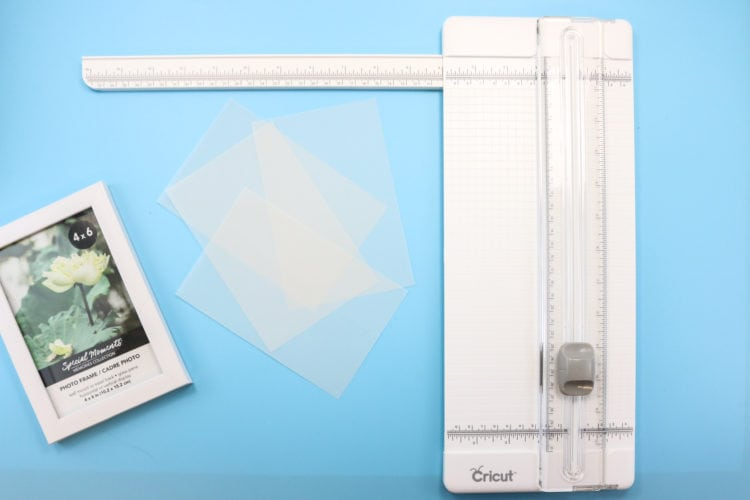 A paper trimmer plus vellum pieces that have been cut to fit frame