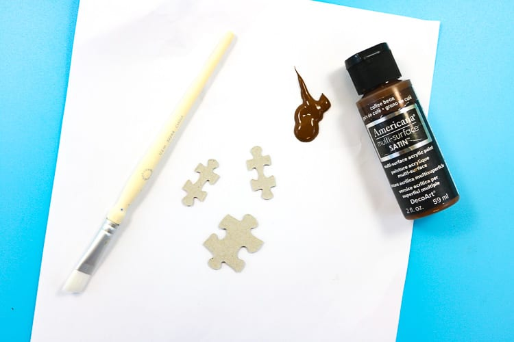 Puzzle pieces being painted brown to become reindeer ornaments