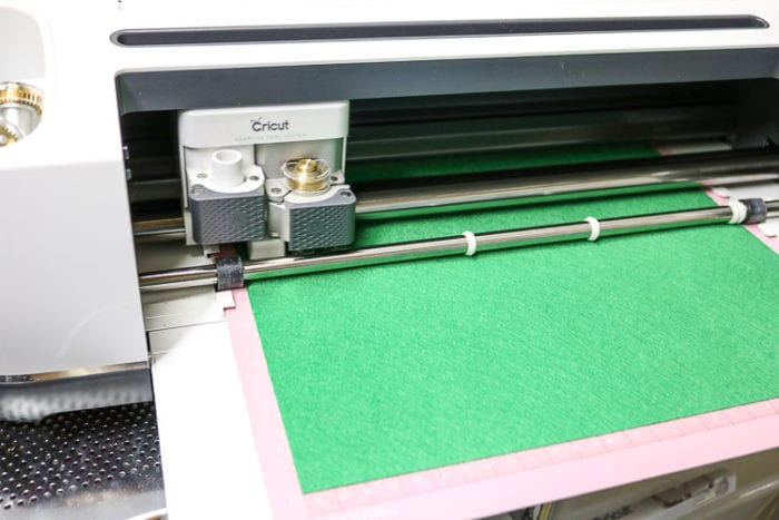 Close up of Cricut Maker carriage cutting Green Felt using Rotary Blade on the Pink Fabric Mat