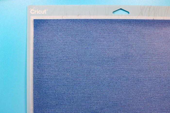 Glitter Vinyl cut with a design on a Blue Cricut Mat