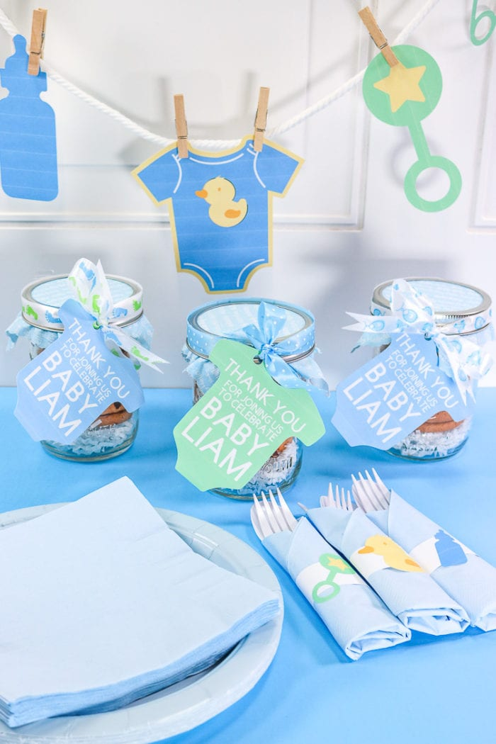 Print then cut Banner, shower favors and napkin rings for baby shower on a white background with blue surface