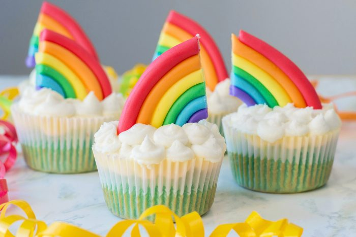Cupcakes in land, sky and clouds with rainbow accents on top.