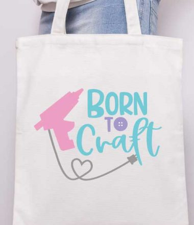 """Vertical - Someone holding a canvas tote with the """"born to craft"""" svg design with glue gun applied in iron vinyl"""