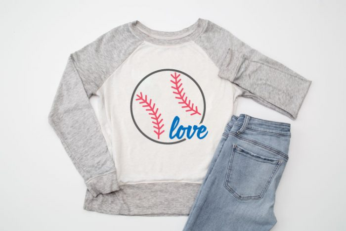 Raglan sweatshirt with grey sleeves and white body with Baseball Love SVG design staged next to a pair of jeans