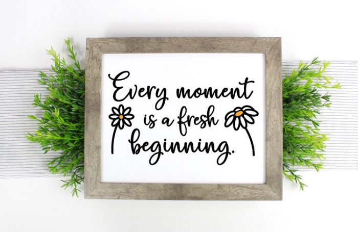 Farmhouse sign on greenery on a table runner with Every Moment is a fresh beginning in vinyl