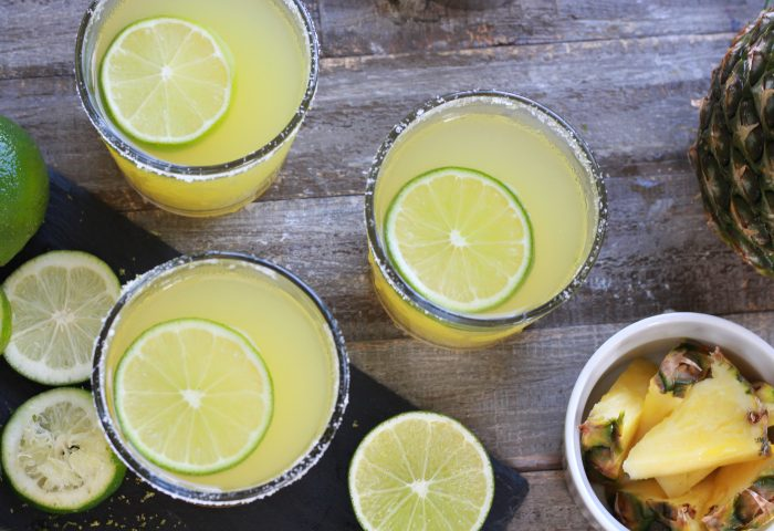 Three Pineapple Margaritas with sliced limes and fresh cut pineapple - Top down shot