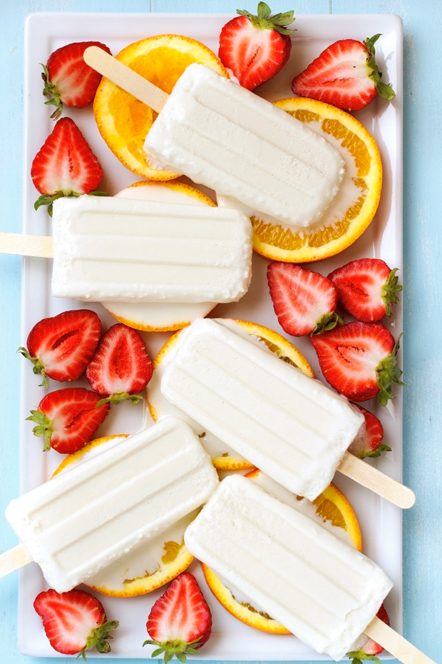 Coconut pops on a bed of orange and strawberies