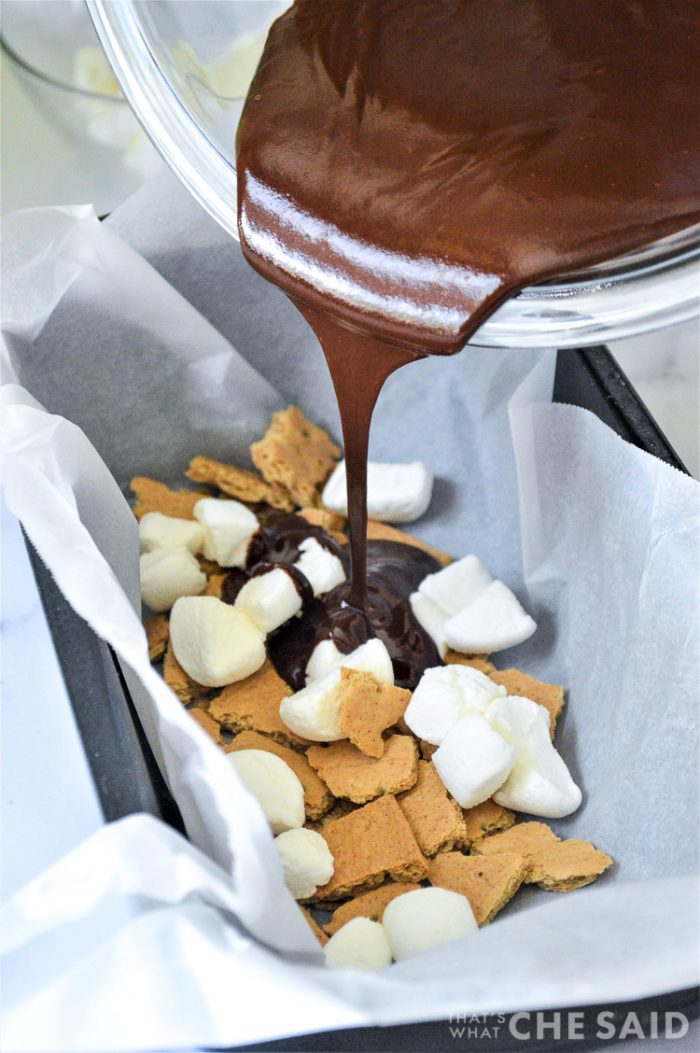 Pouring melted chocolate over marshmallow and graham cracker pieces in parchment lined loaf pan