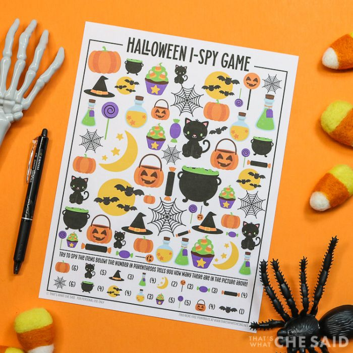 Orange background with Halloween I-spy printable and a pen and halloween decorations around it - square orientation