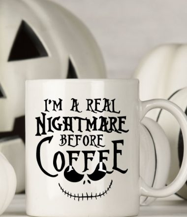 "White mug with black and white halloween decor behind. Mug Reads"" I'm a Real Nightmare Before Coffee"""