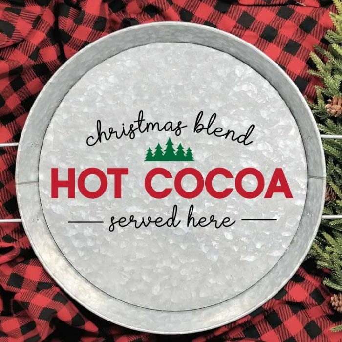 """Galvanized Serving Tray with """"Christmas Blend Hot Cocoa Served Here"""" SVG applied in adhesive vinyl on a red and black buffalo check blanket with some greenery in square format"""