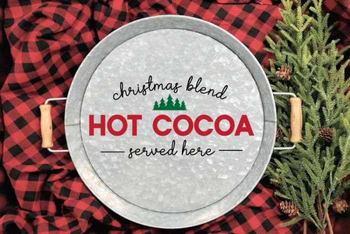 """Galvanized Serving Tray with """"Christmas Blend Hot Cocoa Served Here"""" SVG applied in adhesive vinyl on a red and black buffalo check blanket with some greenery in horizontal format"""
