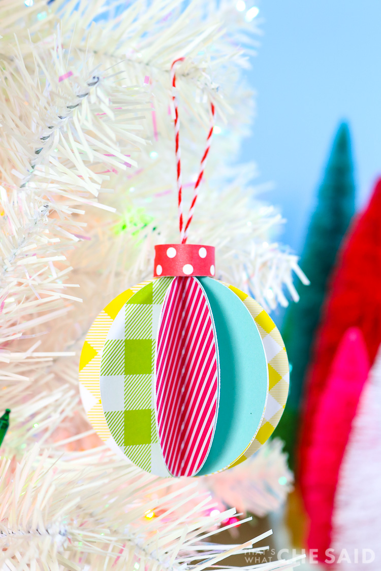 Blue Background, white artificual tree with bottle brush trees in background. Foreground is 3D paper ornament - vertical orientation