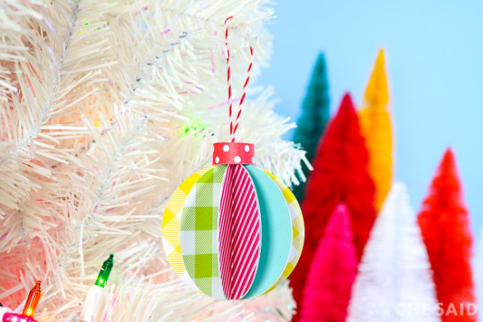 Blue Background, white artificual tree with bottle brush trees in background. Foreground is 3D paper ornament - horizontal orientation