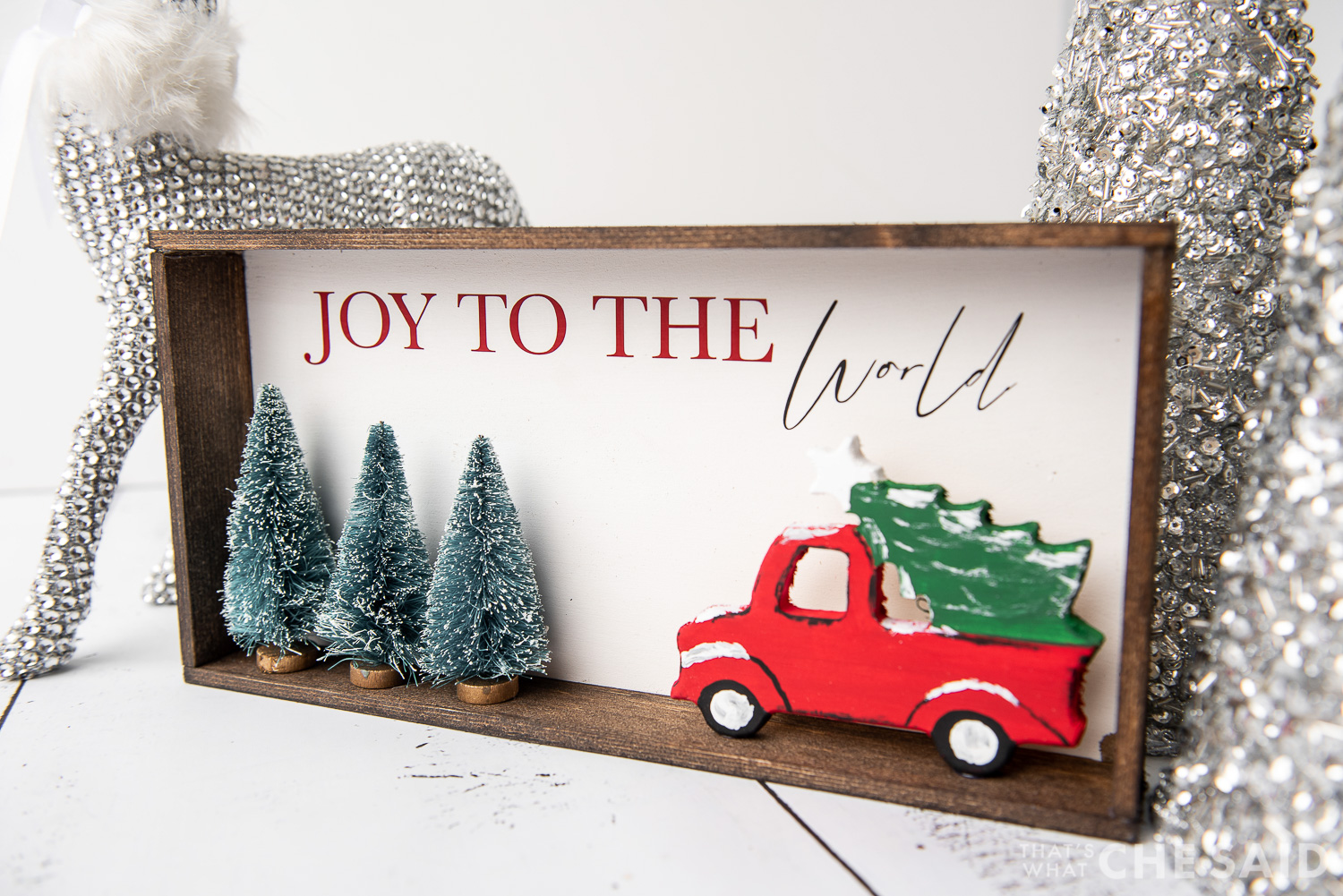 DIY Christmas Sign with Silver trees and deer in background - horizontal at slight angle