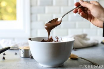 a woman holding a spoon of melted chocolate dripping back into a bowl