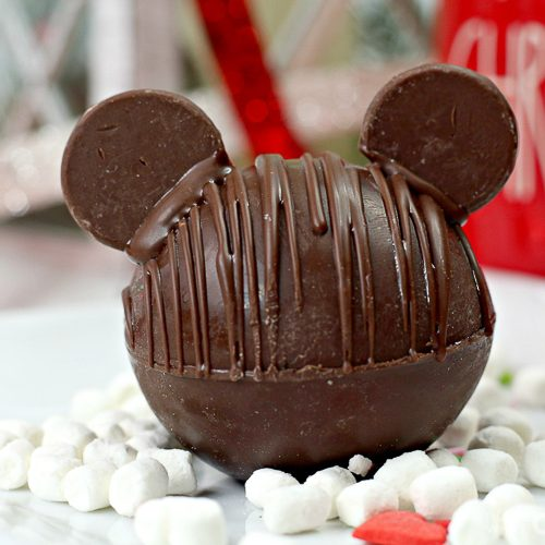 Chocolate Hot Chocolate Bomb with added chocolate wafers as ears to resemble Mickey Mouse with marshmallows and Christmas decor in background horizontal orientation