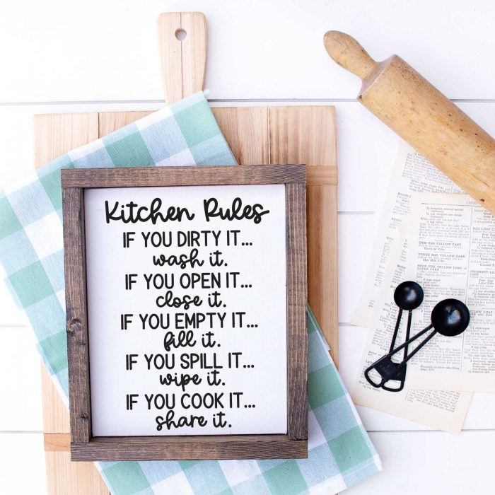 White wood with Cutting Board, kitchen towel, meansuring spoons, rolling pin and sign that has kitchen rules svg applied in Square format