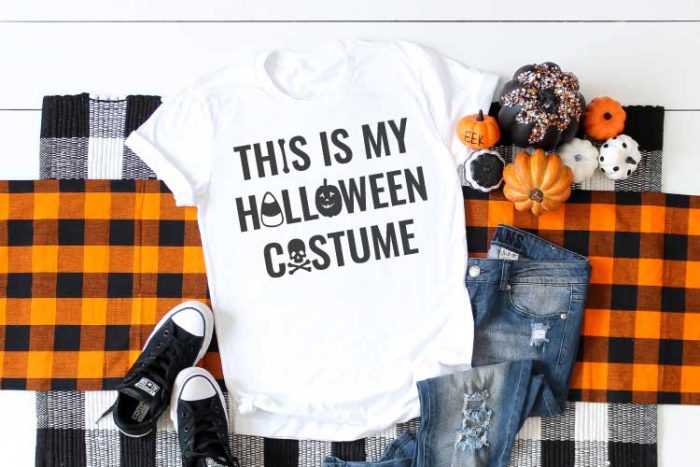 White shirt with Halloween SVG on plaid runner with jeans and t-shirt