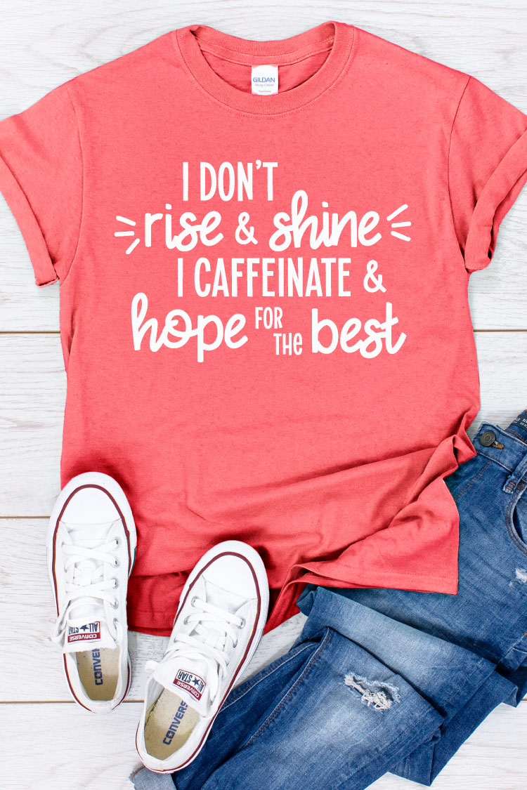 """Coral shirt, jeans and white converse with """"I don't rise and shine I caffeinate and hope for the best"""" written on the shirt in vertical format"""