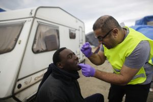 In this Saturday, Nov. 7, 2015 photo dentist Raid Ali treats a migrant with toothache inside France's biggest refugee camp near Calais, northern France. Improvised clinics have appeared from nowhere in the Calais' migrant camp, where medical care for an estimated 6,000 souls depends on volunteers from several countries. (AP Photo/Markus Schreiber)
