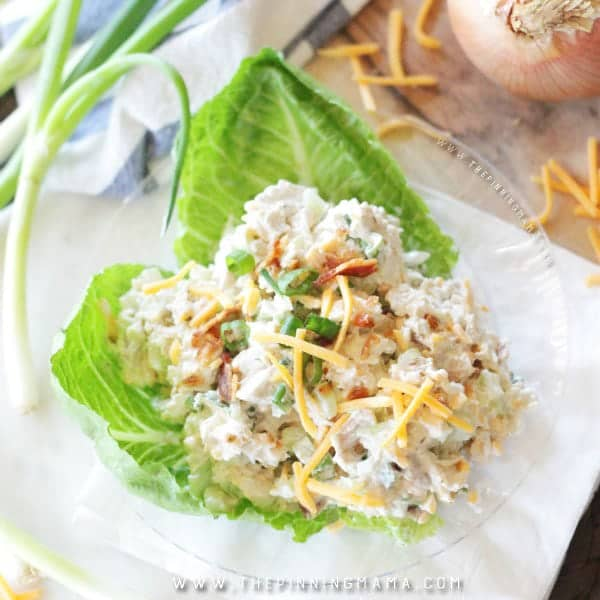 Close up highlighting the garnish on this chicken salad showing cheese and chives and bacon
