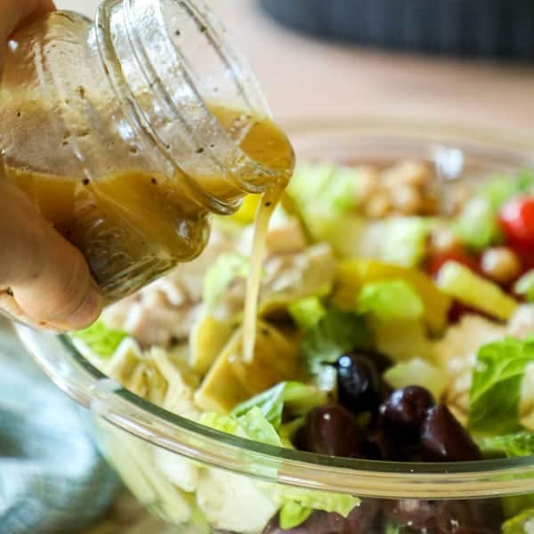 Pouring Homemade Greek Dressing Recipe on Salad