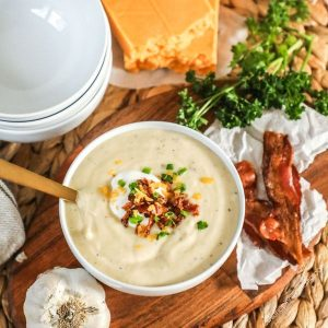 Instant Pot Cauliflower Soup topped with sour cream , cheese and bacon