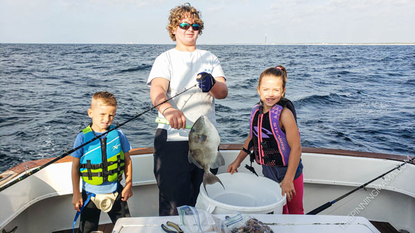 Kids with the trigger fish they caught on the deep sea fishing trip