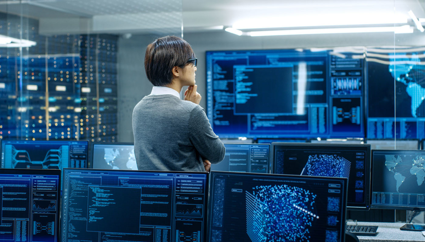 In the System Control Room Technical Operator Stands and Monitor